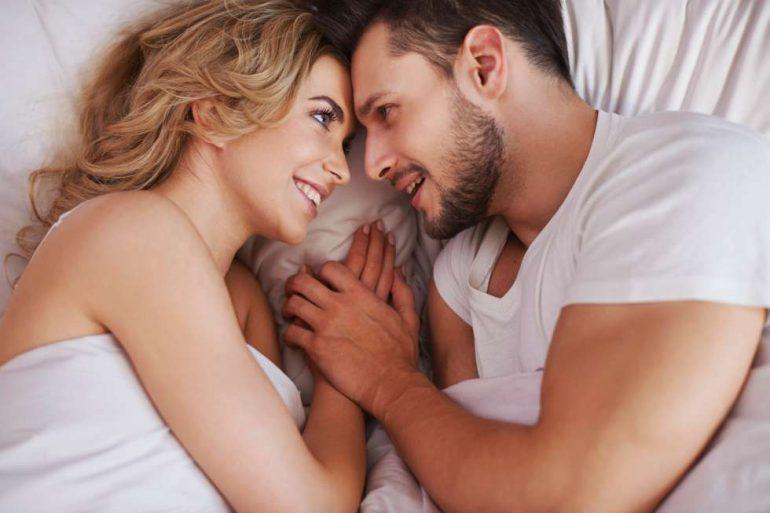 Casal sorrindo na cama | Sexo para tratamento do cálculo renal