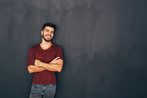 Homem sorrindo encostado na parede | Como é feita a cistoscopia?