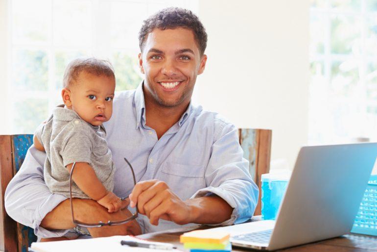 Homem com bebê no colo em frente ao notebook | Sintomas e tratamentos da hipospádia