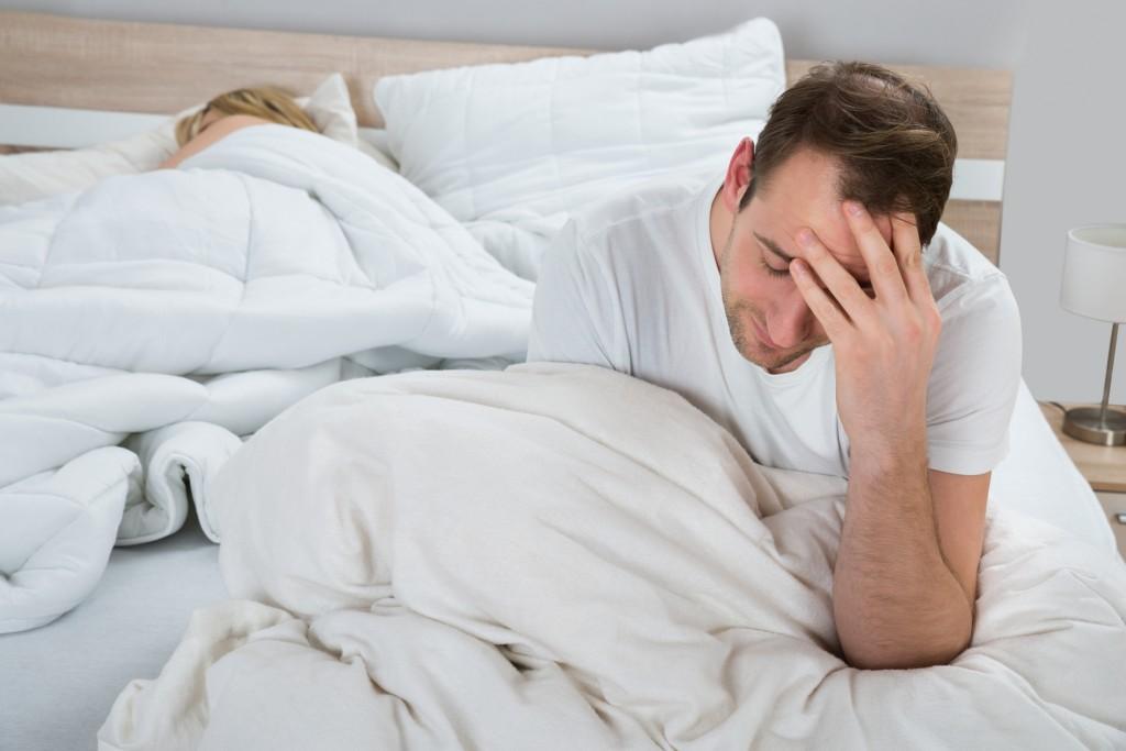 Homem preocupado na cama | Quando se preocupar com a curvatura peniana?