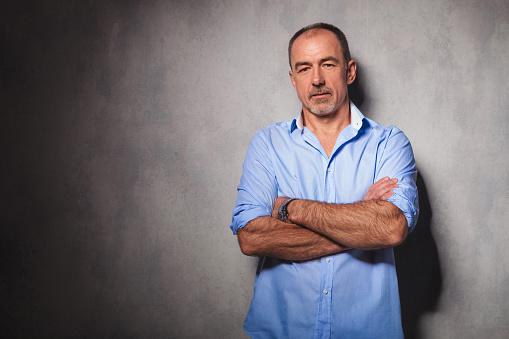 Homem mais velho encostado na parede e com os braços cruzados | Benefícios da prótese peniana