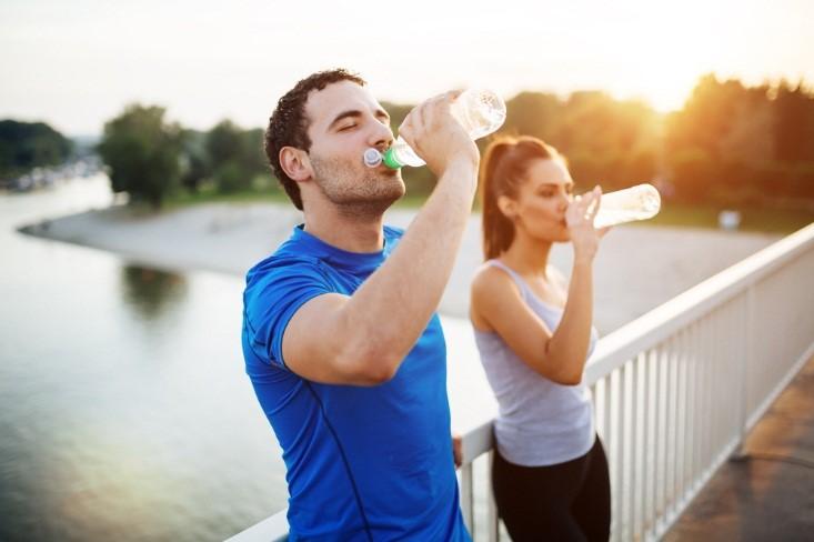 Homem e mulher bebendo água | Como evitar a infecção urinária