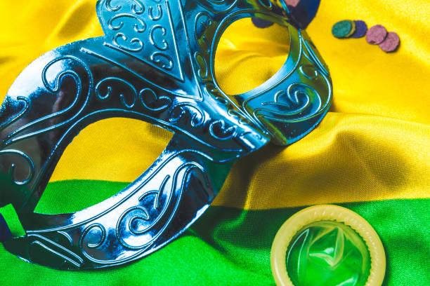 Camisinha e máscara de carnaval em cima da bandeira do Brasil | Carnaval sem DST: vista essa fantasia