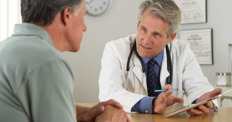 doutor grisalho conversando com paciente em consultório | Doenças penianas causadas por fungos