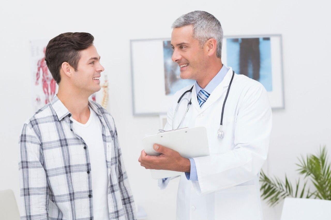 Doutor grisalho conversando com paciente jovem   Doenças penianas causadas por fungos